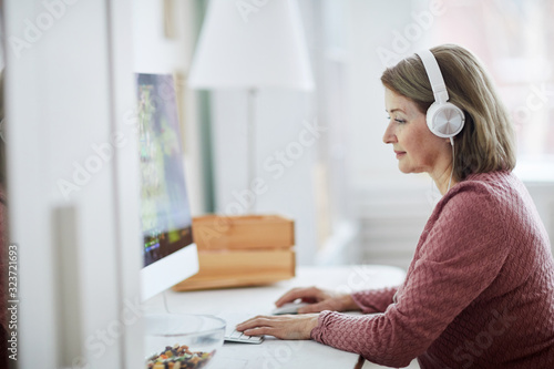 Side view portrait of mature businesswoman using computer while working at home, copy space