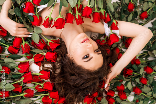 Close-up portrait of a beautiful brunette woman in roses. The girl lies surro...