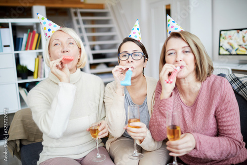 Obraz Portrait of three happy women blowing party horns and looking at camera while celebrating birthday at home - fototapety do salonu