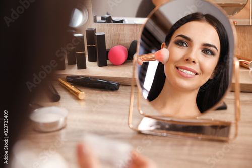 Beautiful young woman applying makeup near mirror at dressing table