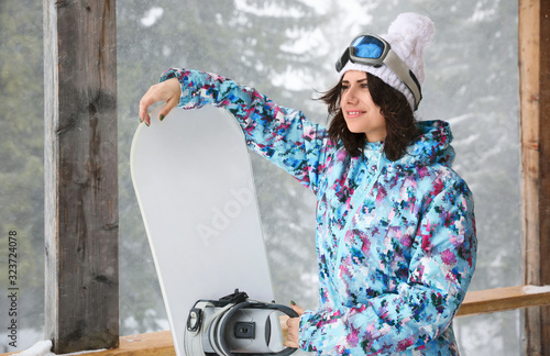 Young woman with snowboard wearing winter sport clothes outdoors