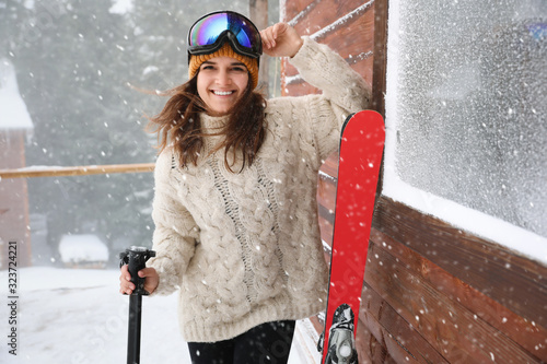 Young woman with skis wearing winter sport clothes and goggles outdoors