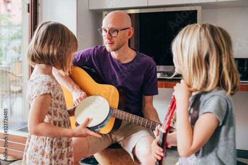 father teaching to his daughters how to play guitar and playing instruments Canvas Print