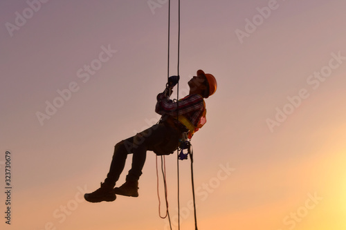 Obraz na plátne Construction worker wearing safety work at high uniform on scaffolding at construction site on during sunset,Working at height equipment