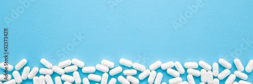 Carta da parati White pills on light pastel blue table