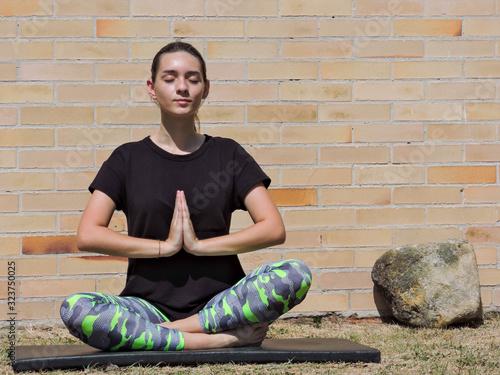 Photo Mujer joven haciendo yoga con camisa negra y fondo de ladrillo
