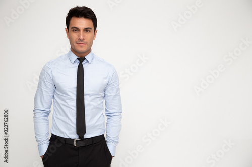 Fotografia Young businessman standing with hands in pocket isolated over white background