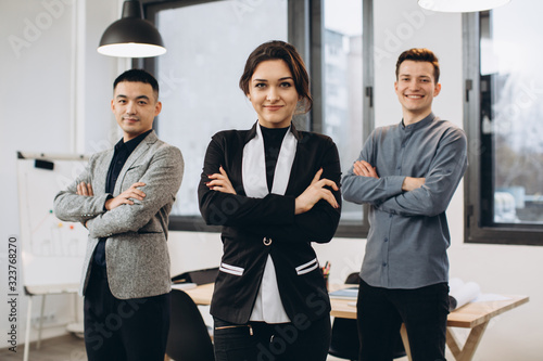 Fototapeta Successful business woman standing with her staff in background at office