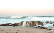 Beautiful Shot Of The Waves Of The Ocean Crashing Into The Rock Formation By The Shore