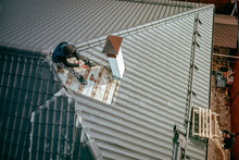 Men Repair The Roof Of The Cottage