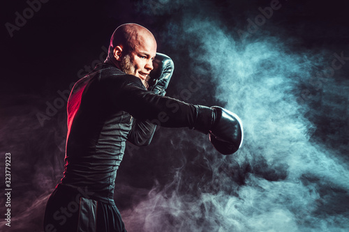 Fotografering Sportsman boxer fighting on black background with smoke