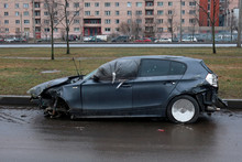 A Car Broken After An Accident With A Dented Hood, Without Front Wheel And With Polyethylene In The Front Door Window