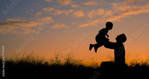 Obraz Happy father playing with his son holding him up in the air. Father son relationship concept.  - fototapety do salonu