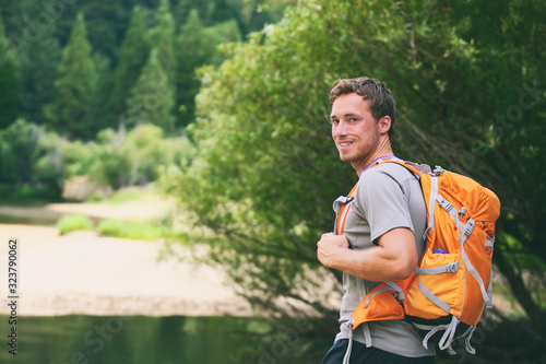 Summer camp young man on travel hike happy hiker walking with camping backpack in forest trek trail.
