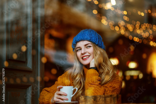 Happy smiling blonde woman drinks coffee or tea in cafe фототапет