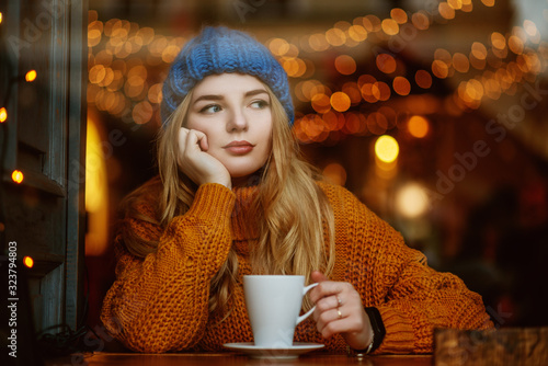 Photo Thoughtful attractive blonde woman  drinks coffee or tea in cafe