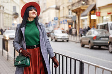 Outdoor Portrait Of Young Happy Smiling Brunette Woman Wearing Orange Hat, Skirt, Green Turtleneck, Checkered Coat, Wrist Watch, With Trendy Reptile Bag, Walking In Street Of European City. Copy Space