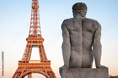 Valokuva Sunset view of the Eiffel Tower with a nude statue of a muscular man, L'Homme, b
