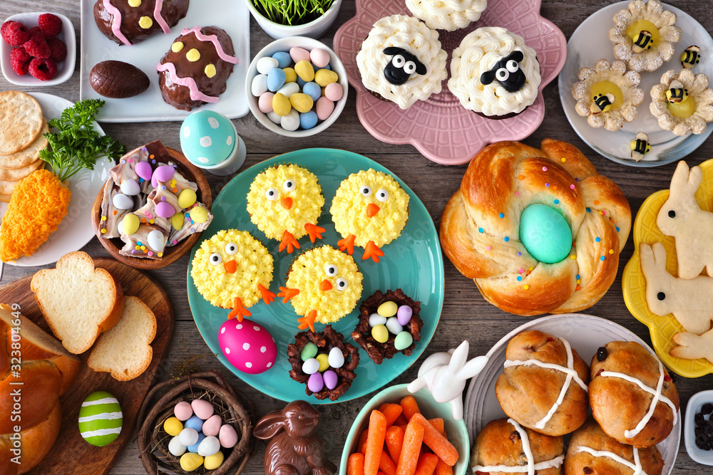 Fototapeta Easter table scene with an assortment of breads, desserts and treats. Top view over a wood background. Spring holiday food concept.