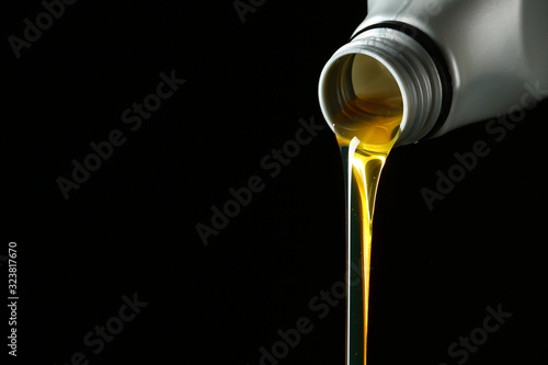 Pouring car oil on dark background
