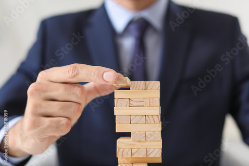Businessman building tower from blocks, closeup. Concept of planning, risk and strategy in business