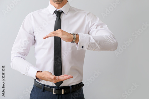 Young businessman holding something on grey background