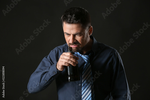 Mature man drinking alcohol on dark background