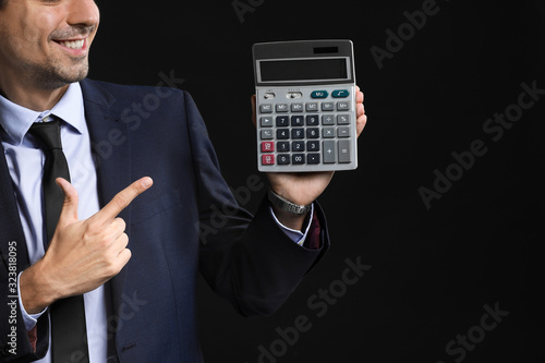 Male bank manager with calculator on dark background