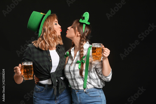 Funny young women with beer on dark background. St. Patrick's Day celebration