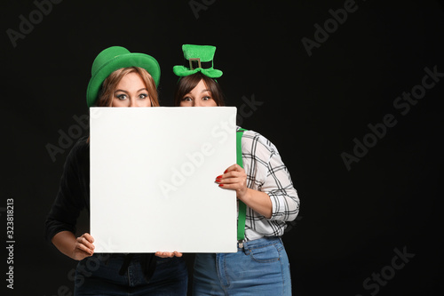 Funny young women with blank poster on dark background. St. Patrick's Day celebration