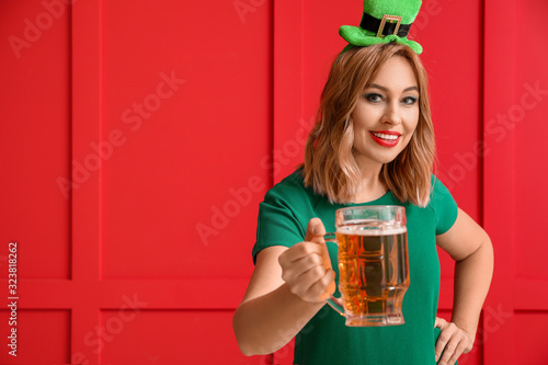 Beautiful young woman with beer on color background. St. Patrick's Day celebration