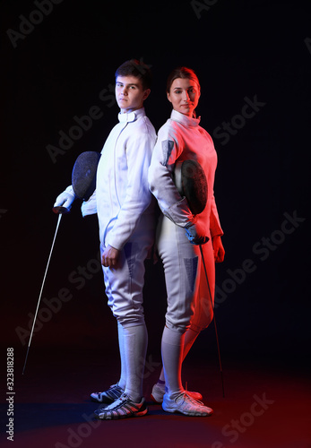 Toned photo of young fencers on dark background