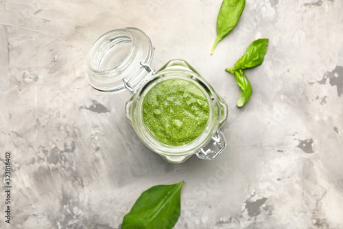 Jar of pesto sauce on grunge background
