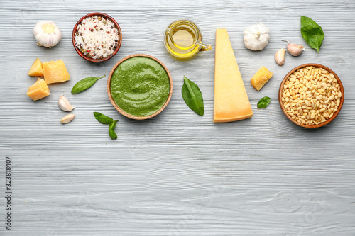Pesto sauce with ingredients on wooden background