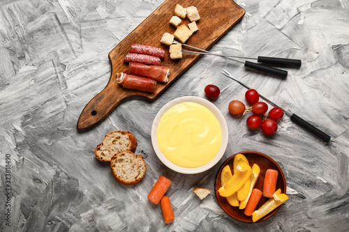 Cheese fondue with snacks on grey background