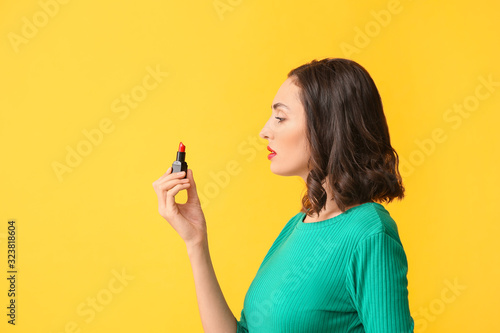 Beautiful young woman applying makeup on color background