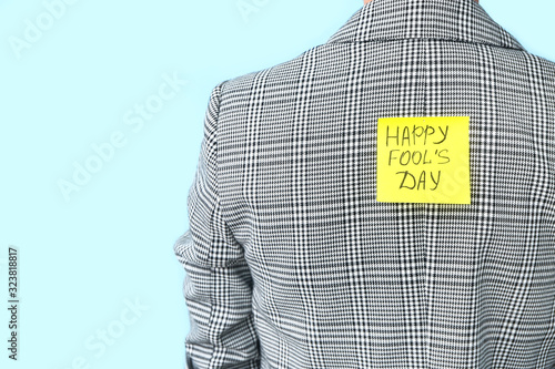 Sticky note with text HAPPY FOOL'S DAY on back of woman against color background. April Fools' Day prank