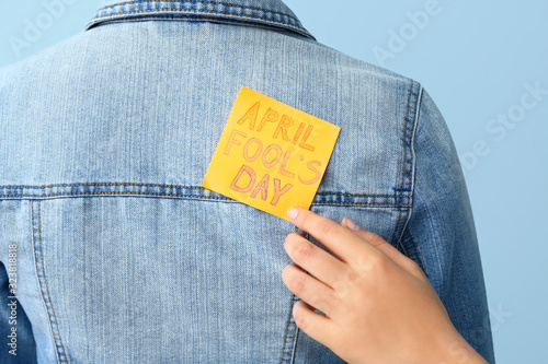 Woman sticking paper to her friend's back against color background, closeup. April Fools' Day prank
