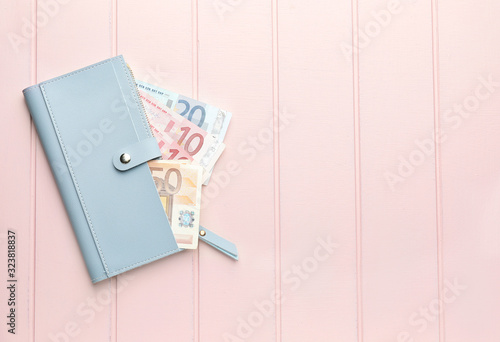 Wallet with money on white wooden background. Savings concept