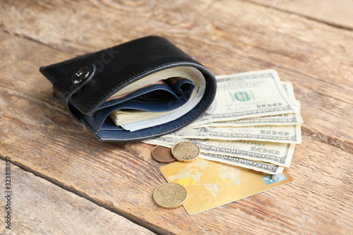 Wallet with money and credit card on wooden background. Savings concept