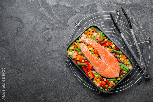 Baking dish with raw salmon steak and vegetables on dark background