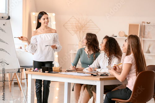 Young woman teaching students in makeup school Wallpaper Mural