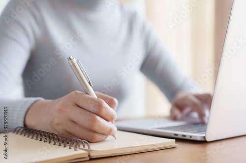 Obraz Hand of business women using laptop and write notebook while sitting working on the desk in the office - fototapety do salonu