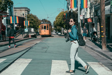 Gay Pride In Castro District Of San Francisco. Young Asian Girl Lesbian Searching Love While Crossing Pedestrian Road In City. Side View Full Length Backpacker Visit Rainbow Town Against Cable Car
