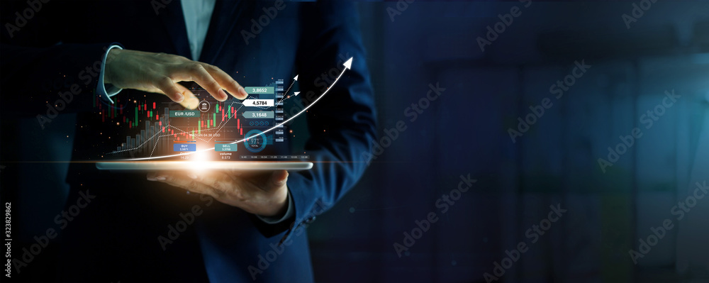 Fototapeta Businessman holding tablet and analysis stock market, currency exchange and banking, showing a growing virtual hologram of statistics, graph and chart, Business growth, planing and strategy  concept.