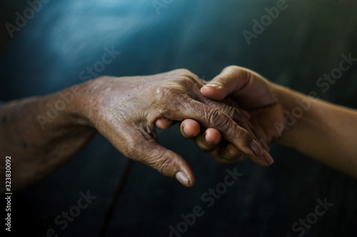 Photo Daughter holding hand of mother elderly that is alzheimer and parkinson patient on dark background