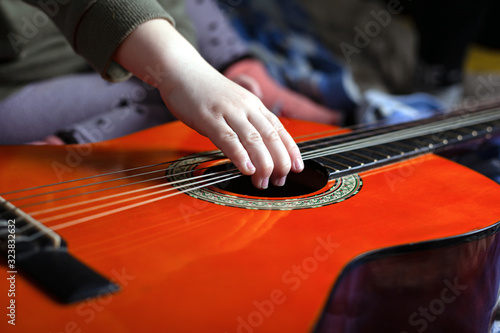 Photo children's hand pulls the strings on an orange acoustic guitar