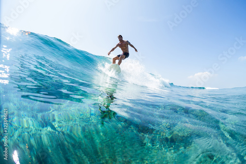 Obraz Surfer rides the glassy ocean wave in tropics - fototapety do salonu