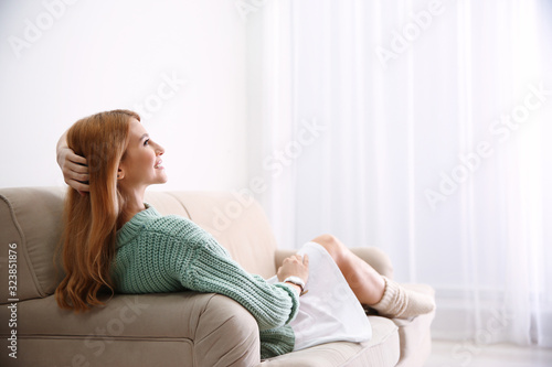 Fototapeta Young woman relaxing on couch at home. Space for text obraz