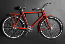 Red Bicycle Hanging On Black Wall Indoors